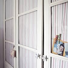 Un armario con cristal y cortinillas de tela